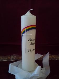 Schöne Taufkerze mit einem Regenbogen und silberfarbenem Kreuz
