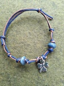 Ein schönes Armband in Blautönen mit einem Metallanhänger als Kleeblatt