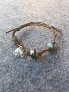 Ein petrolfarbiges Glasperlenarmband mit einem Elefantenanhänger