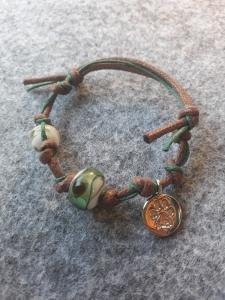 Ein petrolfarbiges Glasperlenarmband mit einem Pfotenanhänger