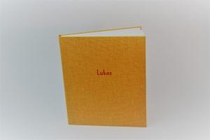 handgebundenes Leporello mit sonnengelben Stoffbezug und mit Titel-Prägung