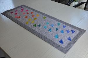 Grauer Patchworktischläufer mit bunten Trapezen im Regenbogenverlauf