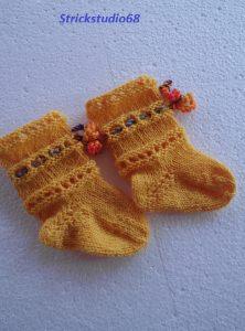 Handgestrickte Babysocken in gelb mit bunter gehäkelter Kordel und einem kleinem Lochmuster  ♥