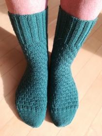 Handgestrickte Socken in grün im Flechtmuster