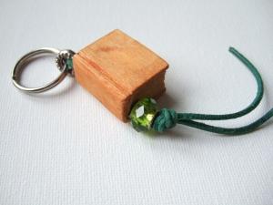 Schlüsselanhänger in Buchform aus Holz in orange mit Perle und grünem Lederband