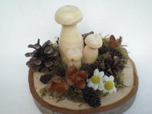 kleine Tischdeko für den Herbst mit hellen gedrechselten Holzpilzen auf einer Astscheibe