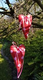 Liebevoll genähte Herzen aus beschichteter Baumwolle –auch für Gartendeko- in rot mit großen rosa Punkten