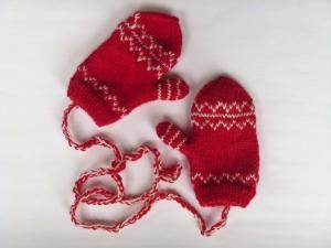 ein Paar handgestrickte Babyhandschuhe mit dezentem Muster in rot- weiß