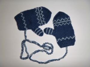 ein Paar handgestrickte Babyhandschuhe mit dezentem Muster in blau - weiß